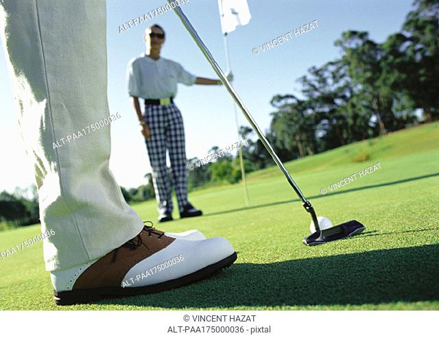 Golfer putting and second golfer holding pole