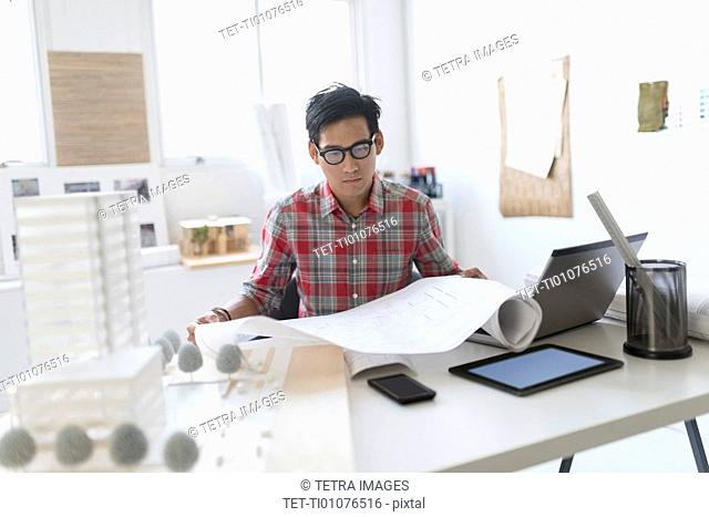 Architect looking at blueprints in office