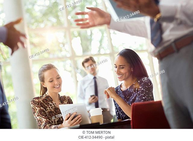 Businesswomen using digital tablet in office meeting