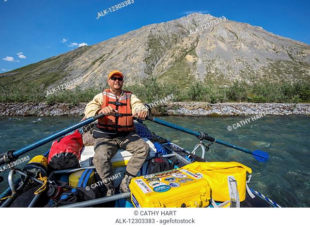 Rafter enjoys a sunny day along the Marsh Fork of the Canning River in the Arctic National Wildlife Refuge, Summer, Alaska