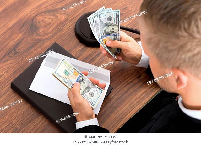 Close-up Of Judge Counting Money At Desk In Courtroom