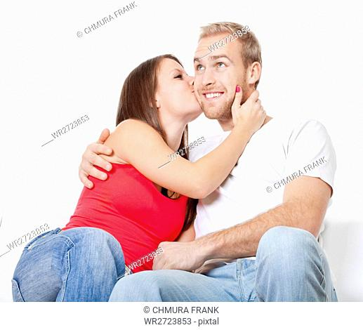 happy young couple - girl kissing boy, embracing - isolated on white