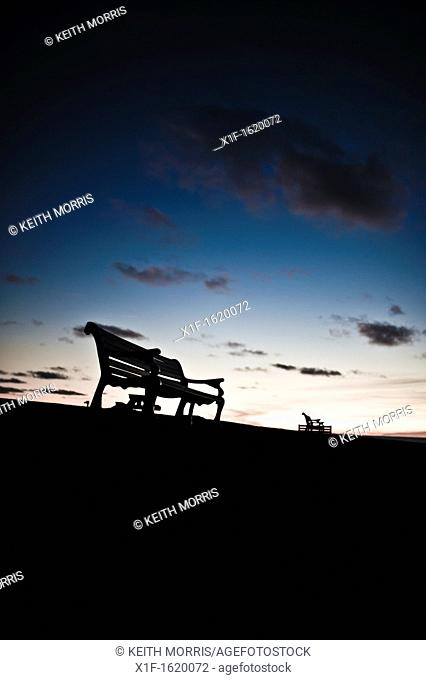 Silhouettes of empty park benches against a twilight sky, UK
