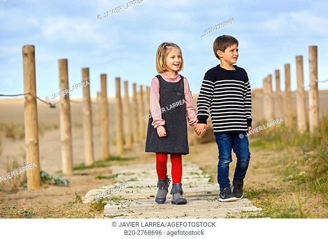 Children walking on the beach, Zumaia, Gipuzkoa, Basque Country, Spain