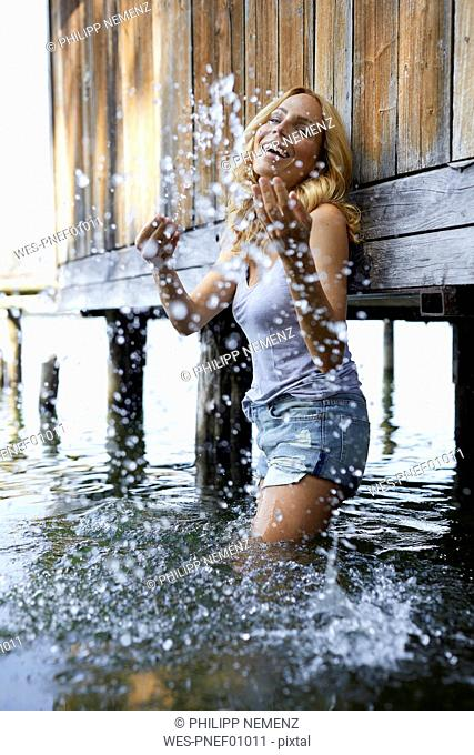 Happy blond woman standing in lake splashing with water