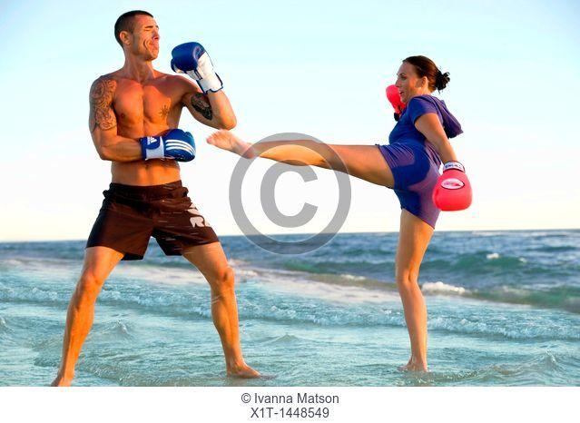 Couple kickboxing on the beach