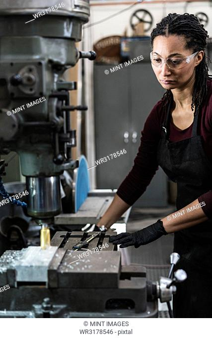 Woman wearing safety glasses standing in a metal workshop, working at a machine
