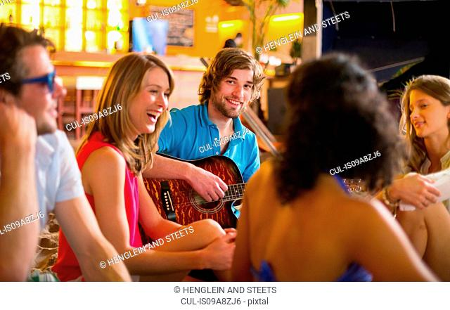 Friends enjoying guitar playing in bar