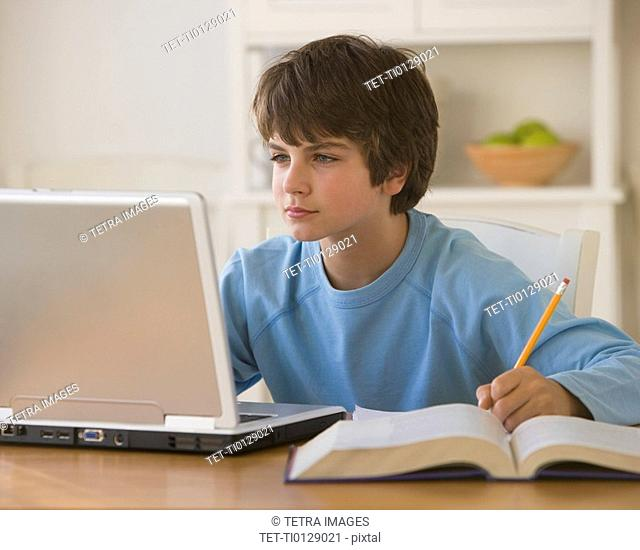 Boy doing homework with laptop