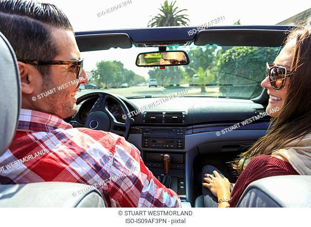 Young couple in convertible, San Diego, California, USA