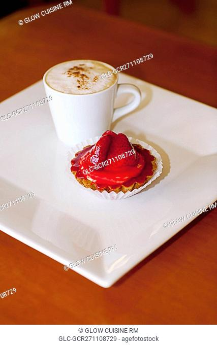 High angle view of a cup of coffee with a strawberry tart