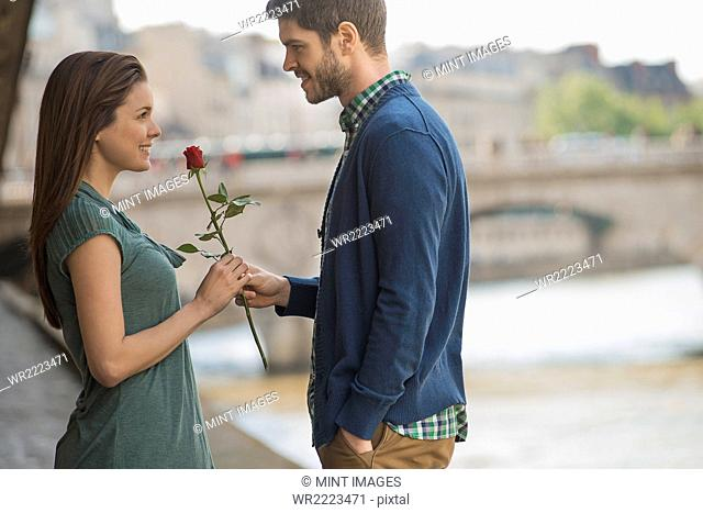 A couple in a romantic setting by a river. A man offering a woman a red rose