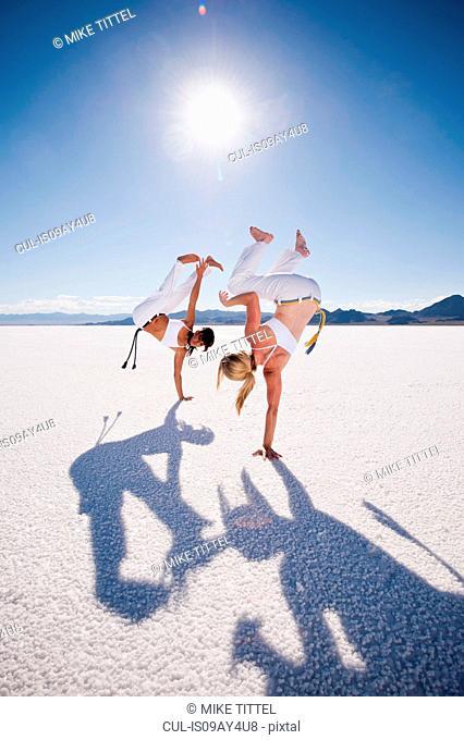 Two women performing capoeira on Bonneville Salt Flats, Utah, USA