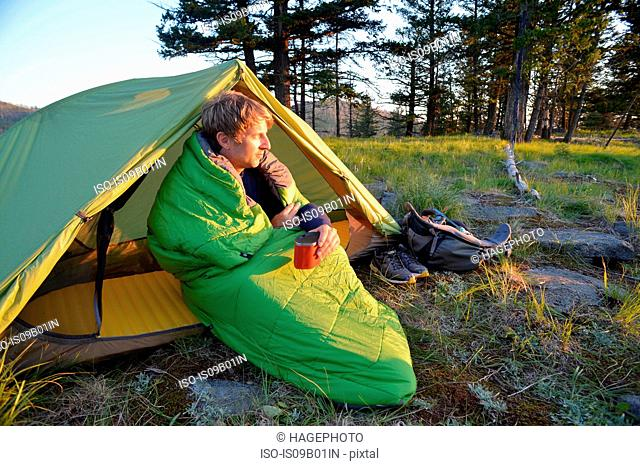 Male camper sitting up in sleeping bag watching sunset on Midnight Ridge, Colville National Forest, Washington State, USA
