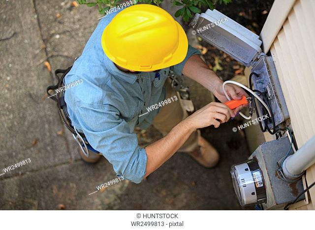 Lineman working on cable at connection box at a home
