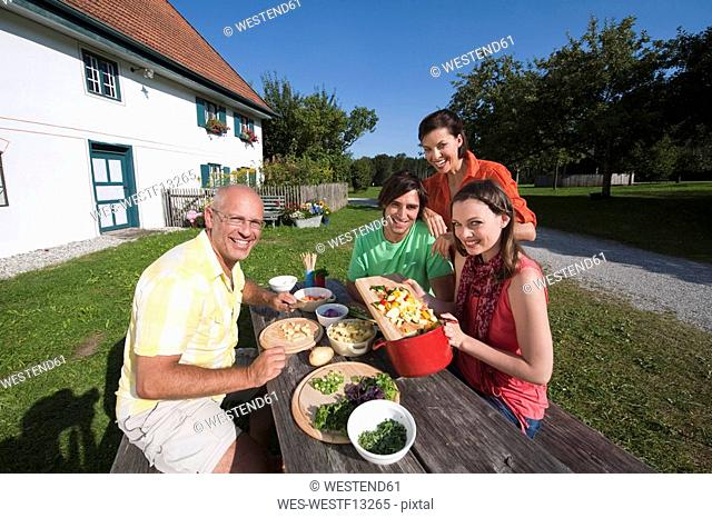 Germany, Bavaria, People at table in garden preparing food