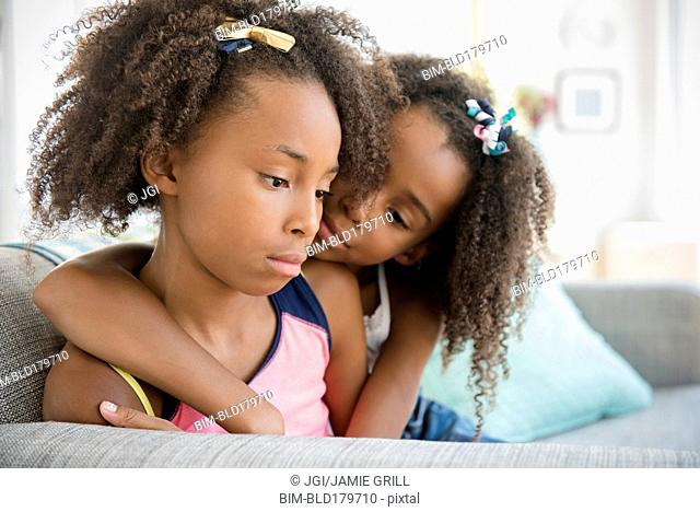 Mixed race sisters hugging on sofa