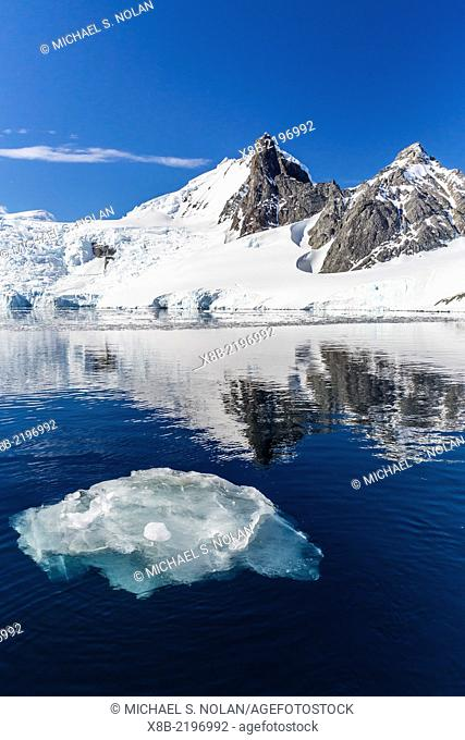 Calm seas reflect snow-capped mountains, Orne Harbor, Antarctica