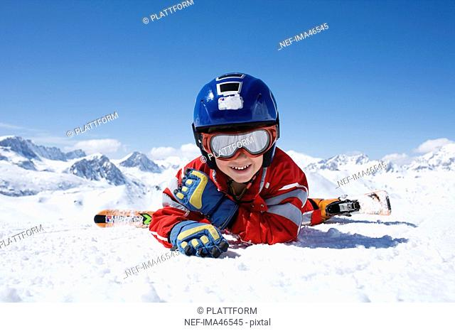 A boy in a skiing outfit resting on the snow