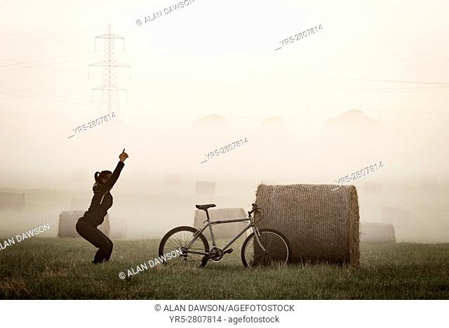 Female mountain biker stretching near Hay bales at sunrise in early morning mist near Billingham, north east England, United Kingdom. United Kingdom