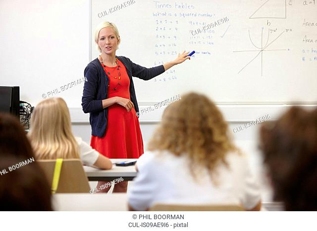 Female teacher using white board in front of class