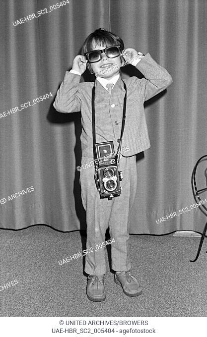 Der Kinderstar Klaus G. Koop mit einer Yashica Mittelformat Kamera zuhause in Nieder-Olm bei Mainz, Deutschland 1960er Jahre. Child star Klaus G