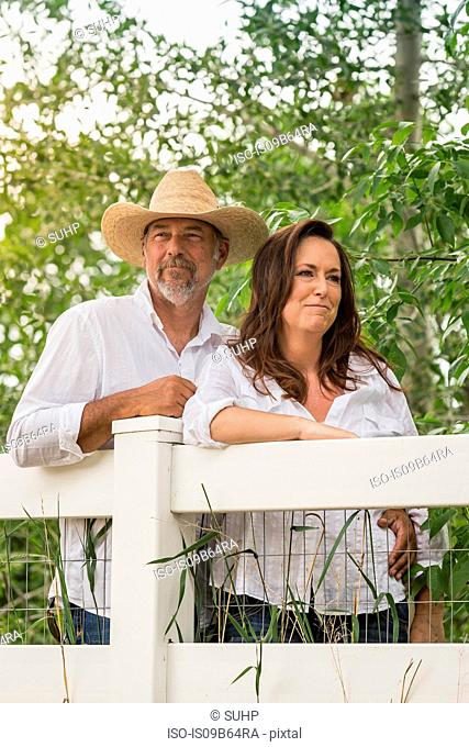Mature couple leaning against ranch fence gazing, Bridger, Montana, USA