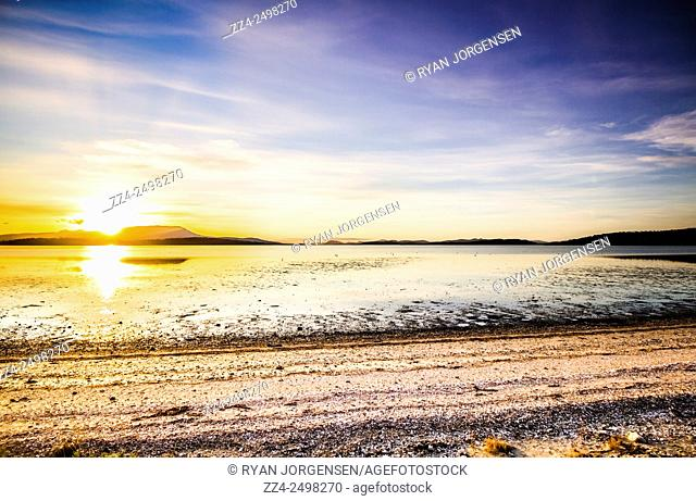 Beach view of a sunset over the shelly shorelines of the tranquil and serene location of South Arm in Southern Tasmania, Australia