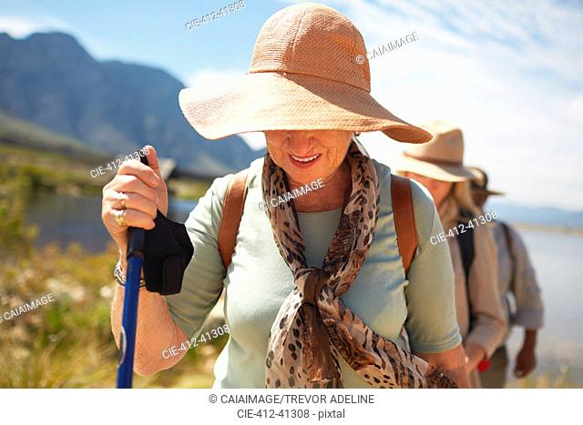 Active senior woman in sun hat hiking