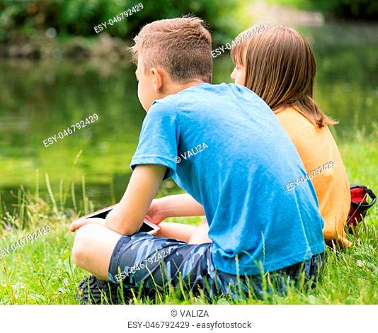 Children - girl and boy, with tablet pc at lakeside. Family - brother and sister, have rest near water in park