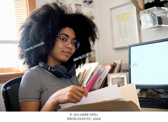 Confident African American woman holding files near computer