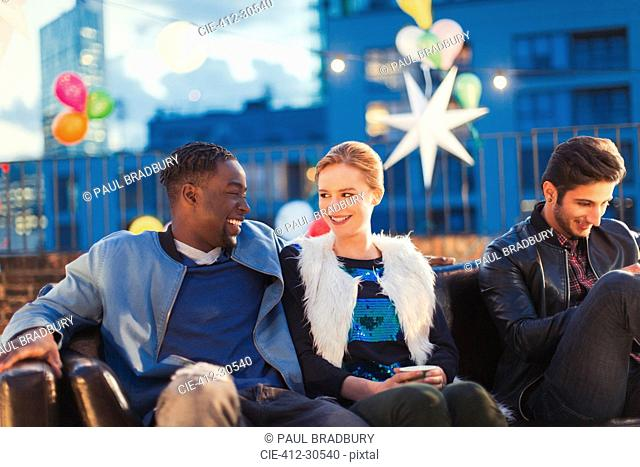 Young man and woman flirting at nighttime rooftop party