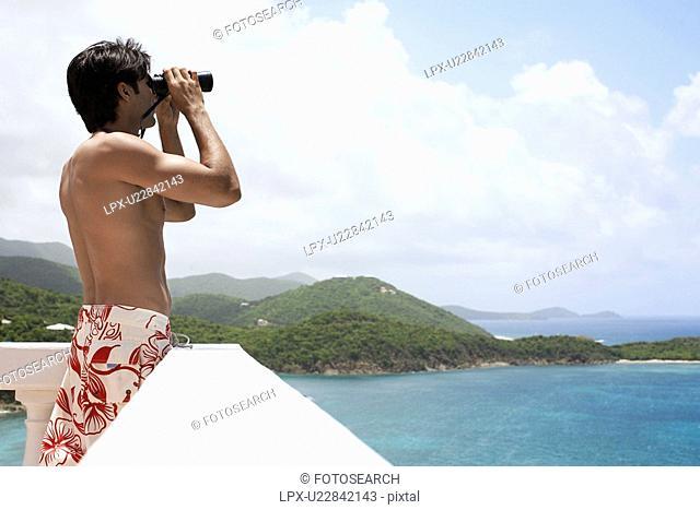 Young man using binoculars at seaside, St. John, US Virgin Islands, USA