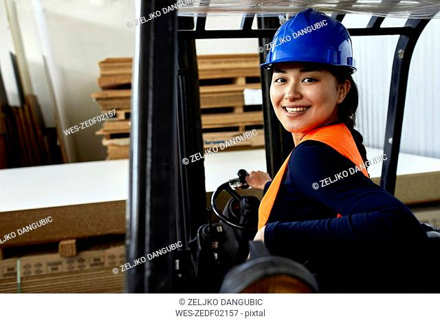 Portrait of confident female worker on forklift in factory