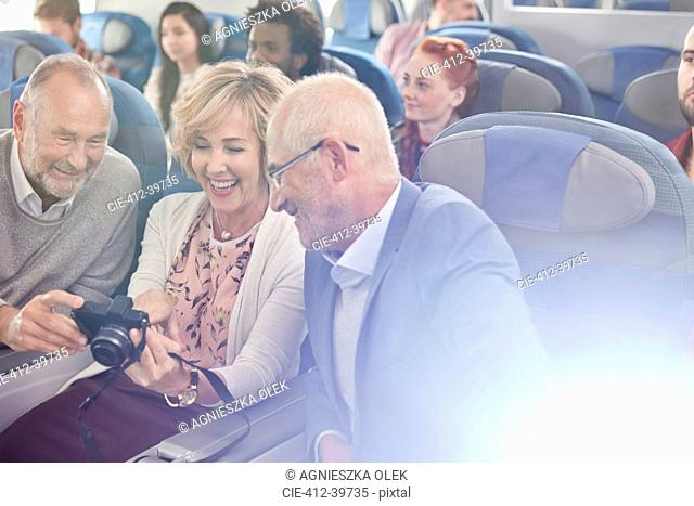 Smiling friends looking at photos on digital camera on airplane