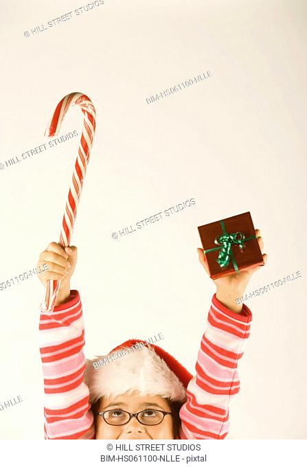 Young girl holding out a candy cane and a Christmas present