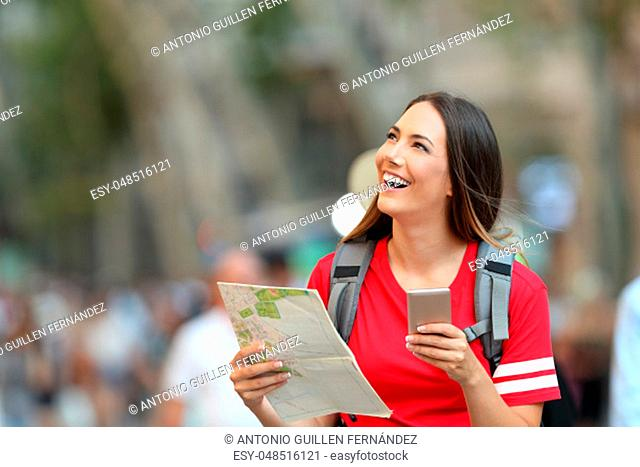 Teen tourist holding a paper guide and a smart phone looking above on the street