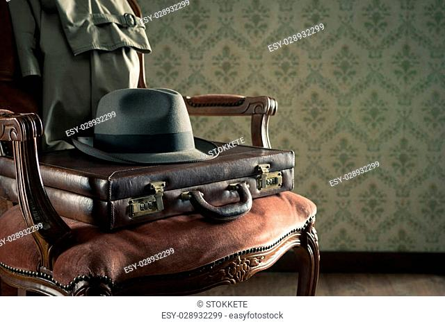Vintage businessman clothing and briefcase on retro chair and vintage wallpaper on background