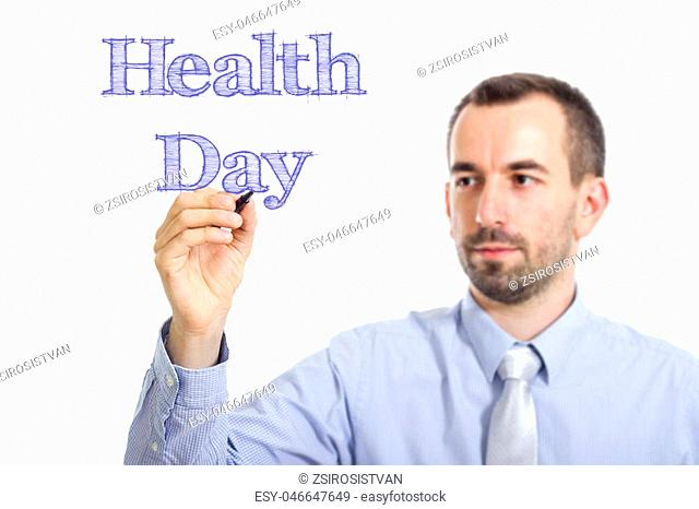 Health Day - Young businessman writing blue text on transparent surface - horizontal image