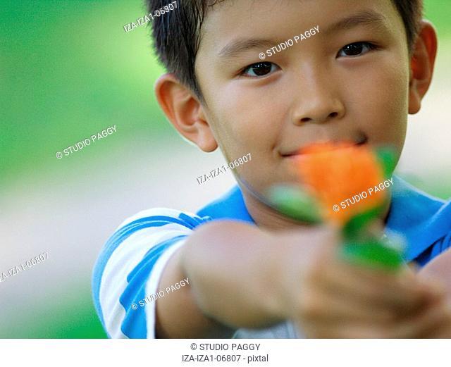 Portrait of a boy holding a flower