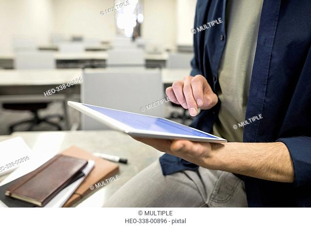 Close up businessman using digital tablet in classroom