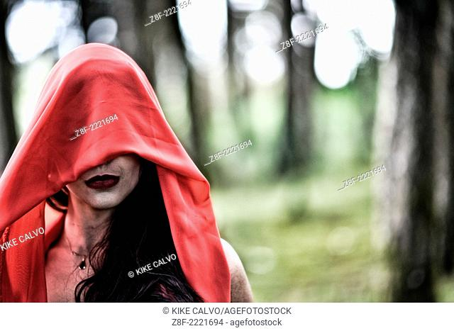 Hispanic woman with a red cloak, recreating a modern fairy tale of Little Red Riding Hood