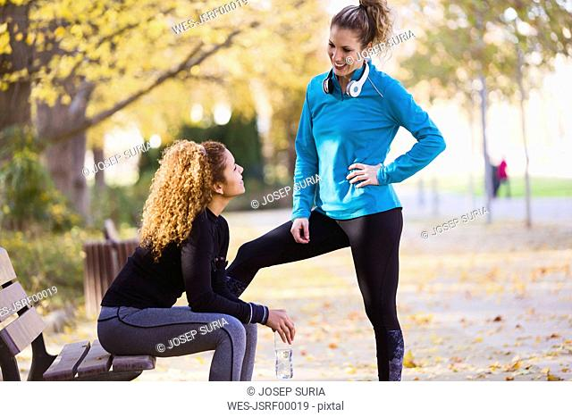 Two sportive young women talking in park