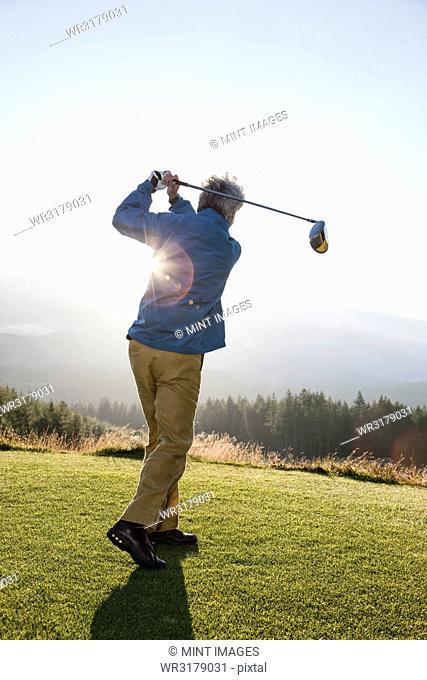 An Asian senior man hitting a drive with a golf club