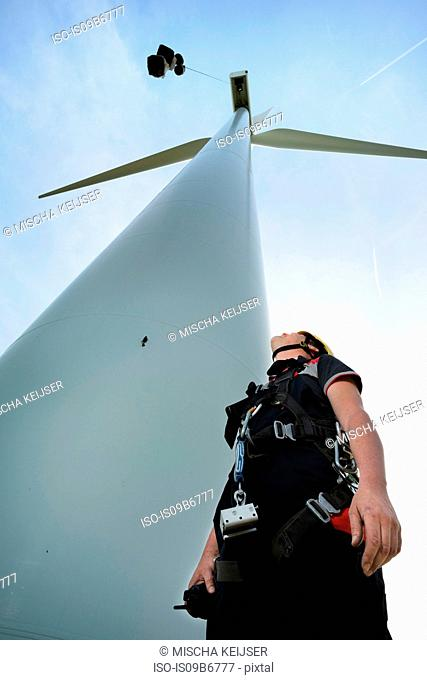 Low angle view of engineer looking up at wind turbine. Terneuzen, Zeeland, Netherlands, Europe