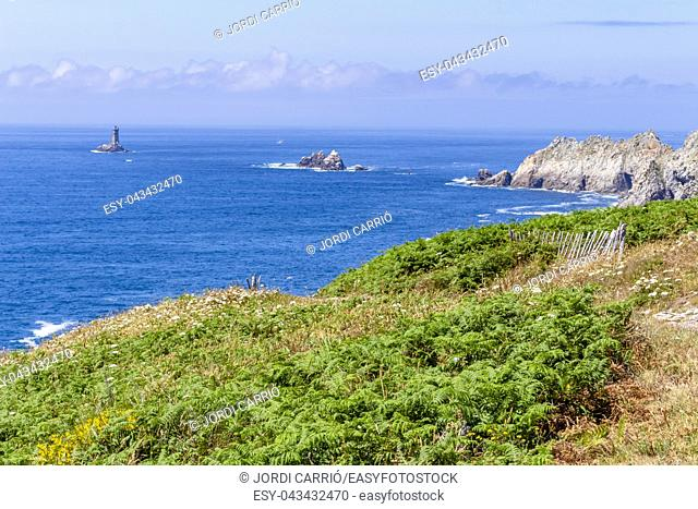View from the tip of Cape Raz, the strait of Sein Island with the old lighthouse in the background, in the French Brittany