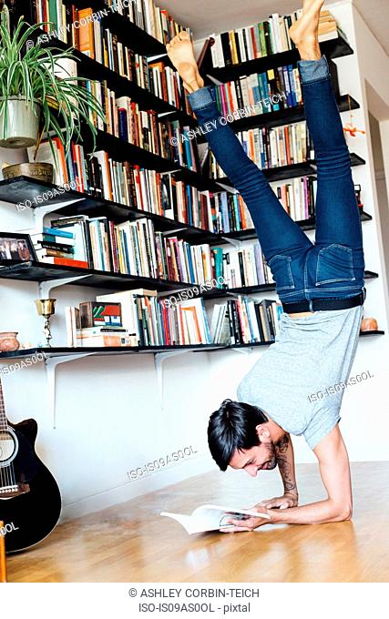 Young man reading book whilst doing forearm stand
