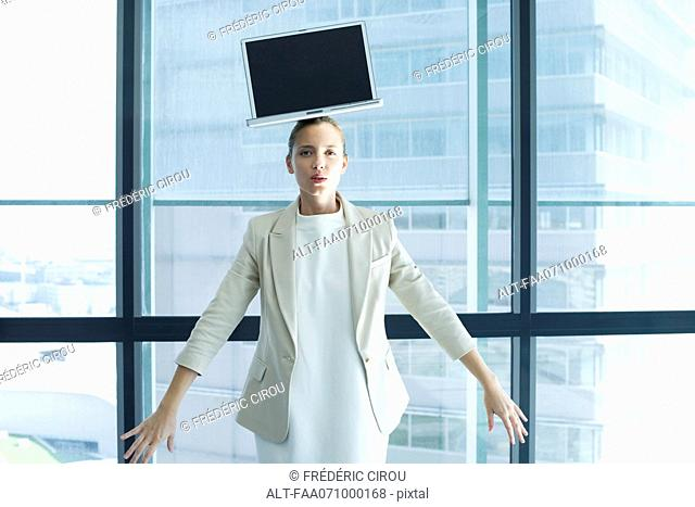 Businesswoman with laptop computer on head