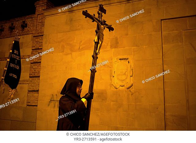A hooded penitent holds a crucifix during an Easter Holy Week procession in Astorga, Castilla y Leon, Spain