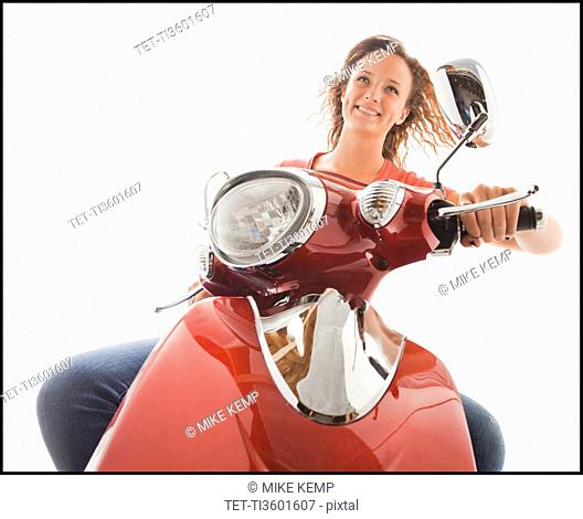 Young girl 16-17 riding scooter